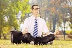 Młody biznesmen sadzający na zielonej trawie medytuje w parku Fotografia Stock