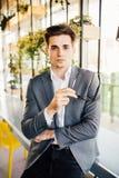 Młody biznesmen siedzi na krawędzi jego drewnianego biurka patrzeje poważnie przy kamerą z szkłami w jego rękach Zdjęcie Royalty Free
