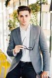 Młody biznesmen siedzi na krawędzi jego drewnianego biurka patrzeje poważnie przy kamerą z szkłami w jego rękach Zdjęcie Stock