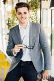 Młody biznesmen siedzi na krawędzi jego drewnianego biurka patrzeje poważnie przy kamerą z szkłami w jego rękach Zdjęcia Stock