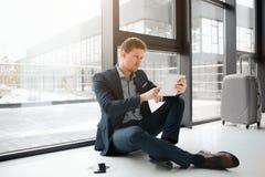Młody biznesmen siedzi na podłodze przy okno Trzyma białą pastylkę i patrzeje swój ekran Facet jest poważny i skoncentrowany zdjęcie stock