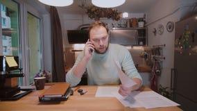 Młody biznesmen siedzi przy stołem, pracuje z papierami i dzwoni someone na smartphone z dokumentami, zdjęcie wideo