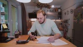 Młody biznesmen siedzi przy stołem, pracuje z papierami i sprawdza coś na telefonie z dokumentami, zbiory wideo
