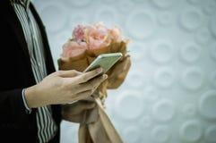 Młody biznesmen trzyma mądrze telefon i różowego róża bukiet w ręce Dla niespodzianki dziewczyny Z kopii przestrzenią zdjęcia royalty free