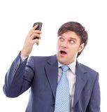 Młody biznesmen trzyma telefon komórkowy i patrzeje zaskakujący Obrazy Royalty Free
