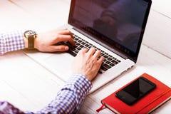 Młody biznesmen używa jego laptop, zamyka up Biznesowi miejsca pracy i biznesu przedmioty Freelancer pracuje w domu Obrazy Stock