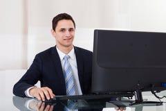 Młody biznesmen używa komputer przy biurowym biurkiem Zdjęcia Royalty Free