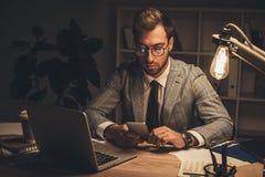 młody biznesmen używa smartphone przy póżno zdjęcia stock