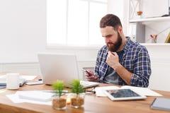 Młody biznesmen w biurowym używa telefonie komórkowym laptopem Obrazy Royalty Free