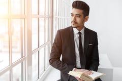 Młody biznesmen w czarnym kostiumu obsiadaniu, czytelniczej książce i patrzeć na okno Obraz Royalty Free