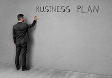 Młody biznesmen w czarnym kostiumu stoi przód betonowa ściana i pisze planie biznesowym, fotografia royalty free