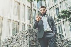 Młody biznesmen w eyeglasses, kostiumu i krawacie, jest stać plenerowy, używać smartphone komputer Obrazy Stock