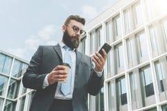 Młody biznesmen w eyeglasses, kostiumu i krawacie, jest stać plenerowy, używać smartphone i pić kawę, Obrazy Royalty Free