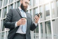 Młody biznesmen w eyeglasses, kostiumu i krawacie, jest stać plenerowy, używać smartphone i pić kawę, Zdjęcie Royalty Free