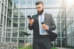 Młody biznesmen w eyeglasses, kostiumu i krawacie, jest stać plenerowy, używać smartphone i pić kawę, Obraz Stock