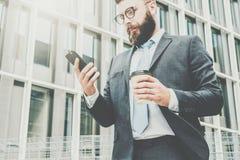Młody biznesmen w eyeglasses, kostiumu i krawacie, jest stać plenerowy, używać smartphone i pić kawę, Fotografia Stock