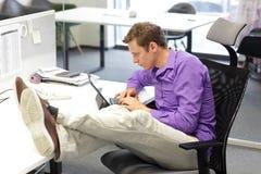 Młody biznesmen w jego biurowym działaniu z pastylką - zła siedząca postura Zdjęcia Royalty Free
