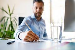 Młody biznesmen w jego biurowym writing coś z ołówkiem Obrazy Stock