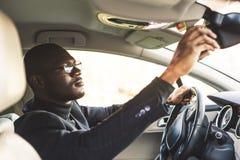 Młody biznesmen w kostiumu obsiadaniu za kołem drogi samochód przystosowywa tylni widoku lustro zdjęcie stock