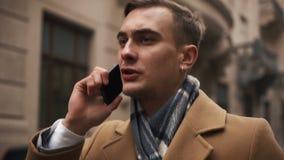 Młody biznesmen w peleryny odprowadzenia puszku ulica w chmurnej pogodzie i opowiadać na telefonie zbiory wideo