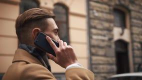 Młody biznesmen w peleryny odprowadzenia puszku ulica w chmurnej pogodzie i opowiadać na telefonie zdjęcie wideo