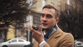 Młody biznesmen w peleryny odprowadzenia puszku ulica w chmurnej pogodzie i opowiadać na telefonie zbiory