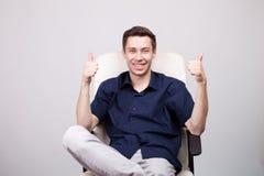 Młody biznesmen w przypadkowej błękitnej koszula pokazuje kciuki do kamery w biurowym krześle podczas gdy siedzący obrazy royalty free