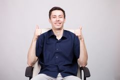 Młody biznesmen w przypadkowej błękitnej koszula pokazuje kciuki do kamery w biurowym krześle podczas gdy siedzący zdjęcie royalty free