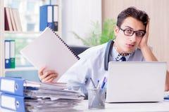 Młody biznesmen w stresie w biurze dostarczać zadania fotografia stock