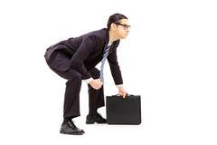 Młody biznesmen w sumo zapaśnictwa postawy mienia walizce Obraz Stock