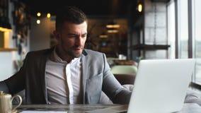 Młody biznesmen w szarym eleganckim kostiumu pracuje przy laptopem w kawiarni blisko okno zbiory