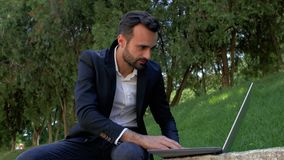 MÅ'ody biznesmen z brodÄ… siedzi w parku na tle traw i drzew i pracuje na laptopie. mężczyzna pisze na zdjęcie wideo