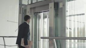 Młody biznesmen z dokumentami czeka windę zbiory wideo
