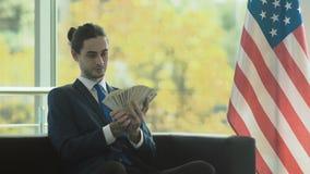 Młody biznesmen z dolarami siedzi w biurze blisko flaga amerykańskiej zbiory