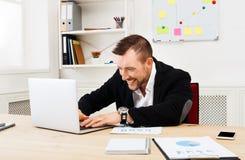 Młody biznesmen z laptopem w biurze zdjęcie stock
