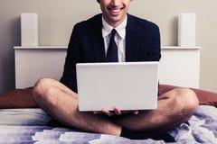 Młody biznesmen z laptopu obsiadaniem na łóżku w jego bieliźnie zdjęcia stock