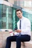 Młody biznesmena chwyt z telefonem komórkowym i filiżanką Zdjęcia Royalty Free