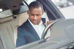Młody biznesmena kierowcy obsiadanie wśrodku samochodowego uczepienie paska dotyczył frontowego outside widok w górę obrazy royalty free