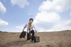 Młody biznesmena klęczenie w mieniu i pustyni teczka, wyczerpująca fotografia stock