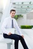 Młody biznesmena obsiadanie na ławce z laptopem Obrazy Stock
