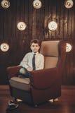 Młody biznesmena obsiadanie przed światło ścianą Obrazy Royalty Free