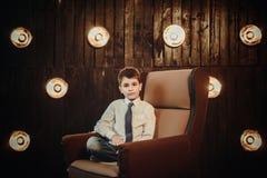 Młody biznesmena obsiadanie przed światło ścianą Fotografia Stock