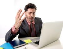Młody biznesmena obsiadanie przy biurowym biurkiem pracuje na komputerowego laptopu desperacki zmartwionym w praca stresie Obraz Stock