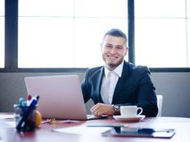 Młody biznesmena obsiadanie przy jego biurkiem z laptopem zdjęcia stock