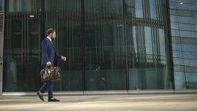 Młody biznesmena odprowadzenie wzdłuż miasto ulicy, patrzeje zegarek w letnim dniu zbiory wideo