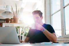 Młody biznesmena pić kawowy i patrzeć laptop Obraz Stock