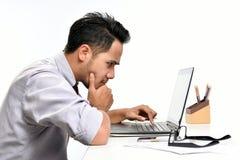 Młody biznesowego mężczyzna główkowanie podczas gdy pracujący z laptopem Zdjęcie Royalty Free