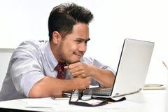 Młody biznesowego mężczyzna główkowanie podczas gdy pracujący z laptopem Obrazy Royalty Free