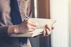 Młody biznesowego mężczyzna ręki czytanie i writing przy okno Obraz Royalty Free