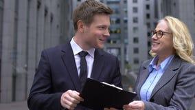 Młody biznesowego mężczyzny i seniora żeński kolega dyskutuje dylowego dokument, praca zbiory wideo